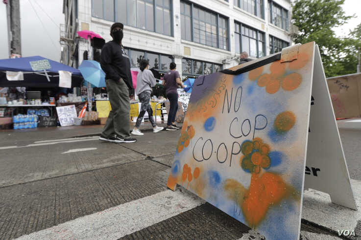 """People walk near what is being called the """"No Cop Co-op"""" were protesters and others can get free food and other supplies"""