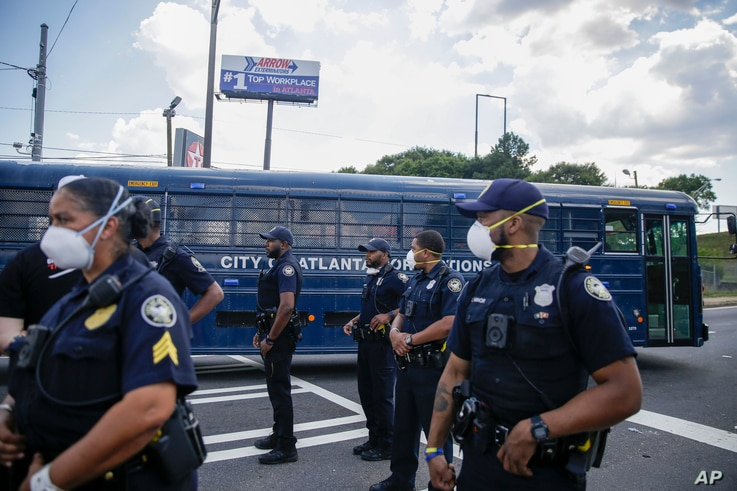 Officers stand by a City of Atlanta Corrections bus near protesters, Saturday, June 13, 2020, near the Wendy's where Rayshard…