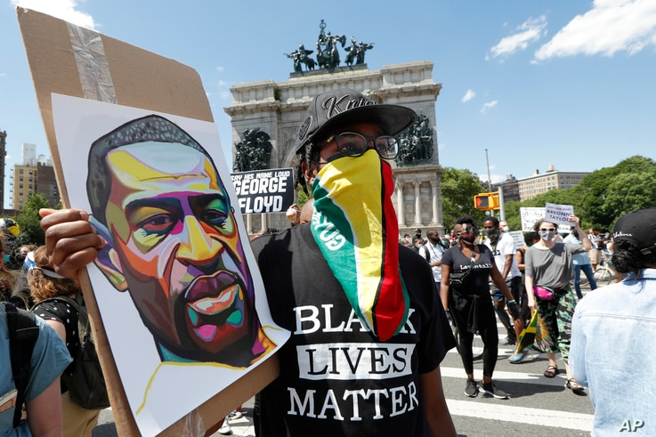 A man wears a Guyanese flag as his face protection as he listens to speakers during a Caribbean-led Black Lives Matter rally.