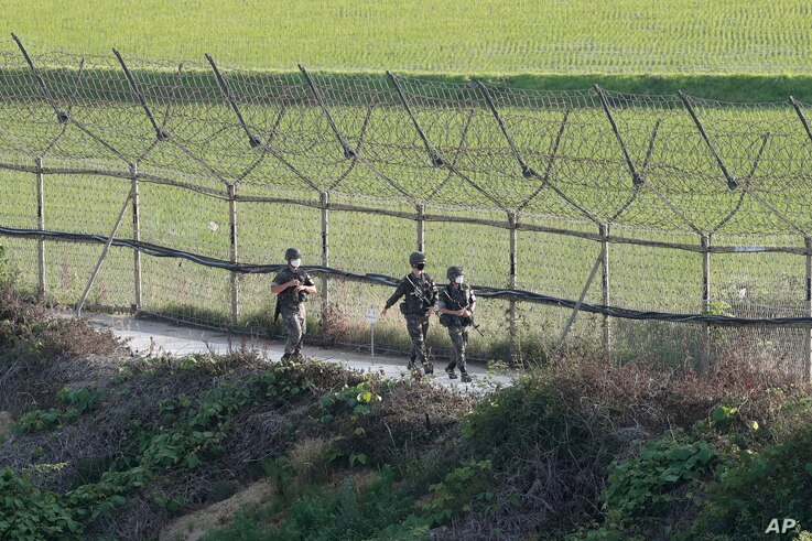 South Korean army soldiers patrol along the barbed-wire fence in Paju, South Korea, near the border with North Korea, Monday,…