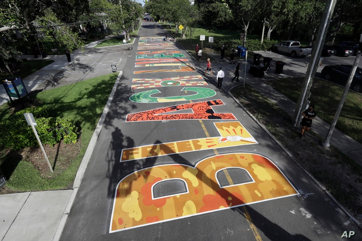 Several local artists painted Black Live Matter mural on the street during a Juneteenth 2020 celebration outside the Dr. Carter G. Woodson African American Museum Friday, June 19, 2020, in St. Petersburg, Fla.
