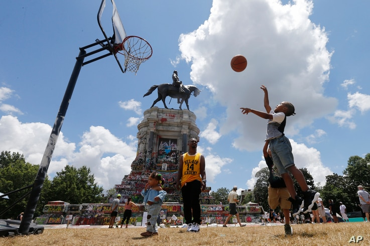 Isaiah Bowen, right, takes a shot as his dad, Garth Bowen, center, looks on at a basketball hoop in front of the statue of Confederate General Robert E. Lee on Monument Avenue in Richmond, Virginia, June 21, 2020.