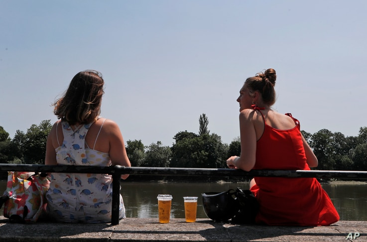 Two women sit with take away drinks from a pub on the banks of the river Thames in London, Tuesday, June 23, 2020. Millions of…