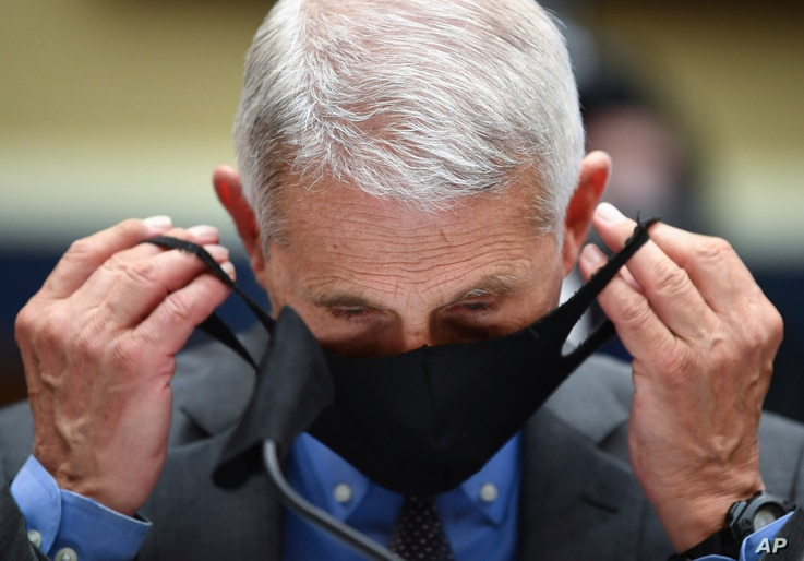 Director of the National Institute of Allergy and Infectious Diseases Dr. Anthony Faucitakes off his face mask before…