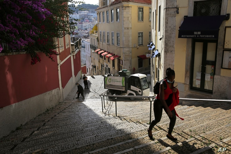 In this photo taken Wednesday, June 24, 2020, a woman wearing a face mask walks past workers washing the street in Lisbon's old…