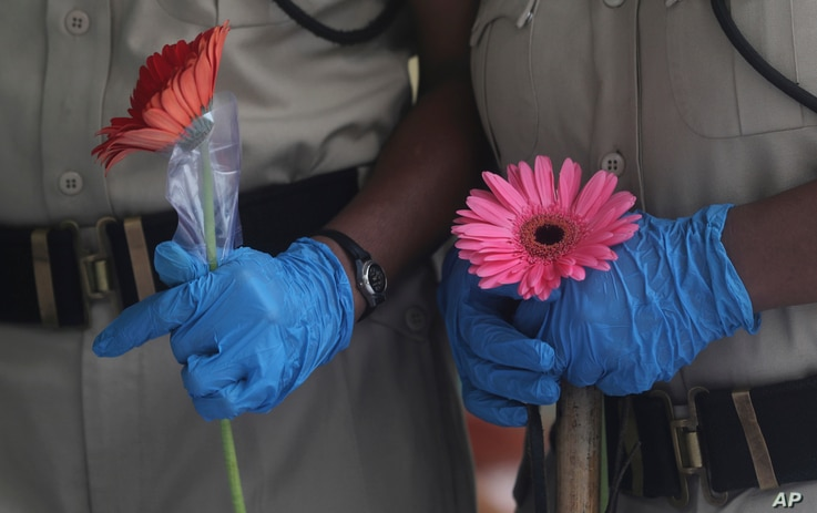 Security officers hold flowers given to them as a gesture of gratitude at the end of a free medical camp in Dharavi, one of…