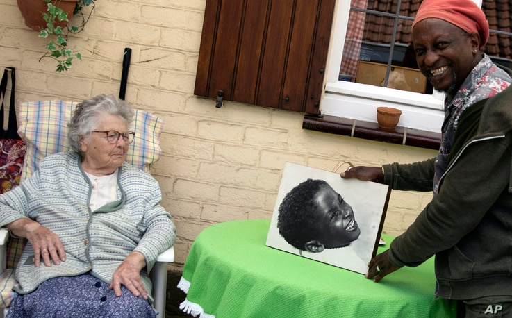 Eric Baranyanka, right, and his foster mother Emma Monsaert look at a photo of Eric as a young boy in Lembeek, Belgium, June 22, 2020.
