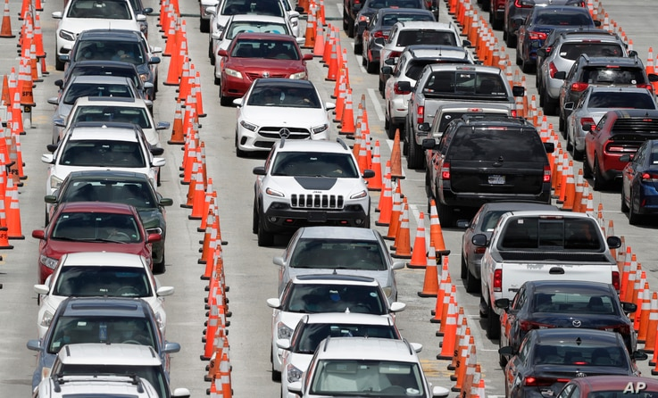 Lines of cars wait at a coronavirus testing site outside of Hard Rock Stadium, Friday, June 26, 2020, in Miami Gardens, Fla…