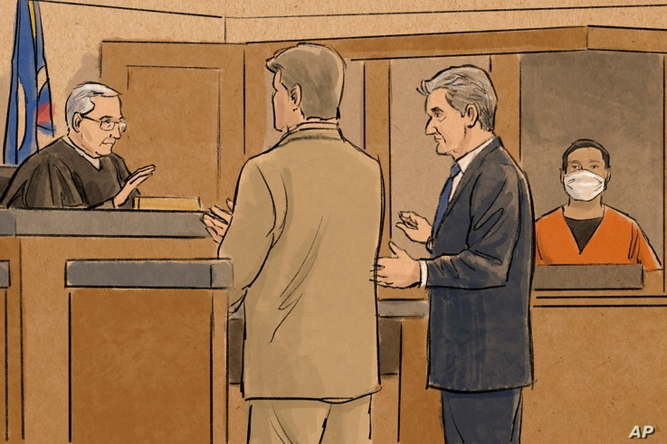 In this courtroom sketch, former Minneapolis police officer Tou Thao, right, watches as his defense attorney, Robert Paule,…