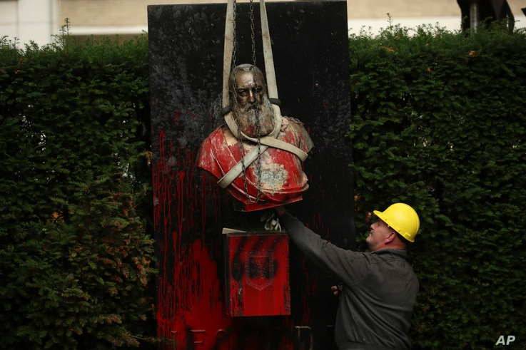 A bust of Belgium's King Leopold II, is hoisted off of its plinth by a crane as it's removed from a park in Ghent, Belgium on…