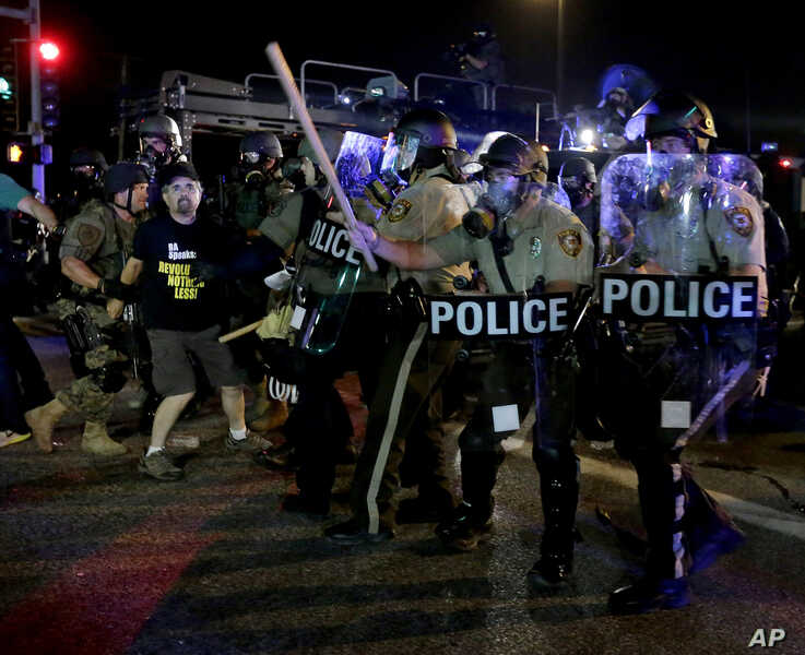 A man is detained after a standoff between protesters and police Aug. 18, 2014, during a protest for Michael Brown.