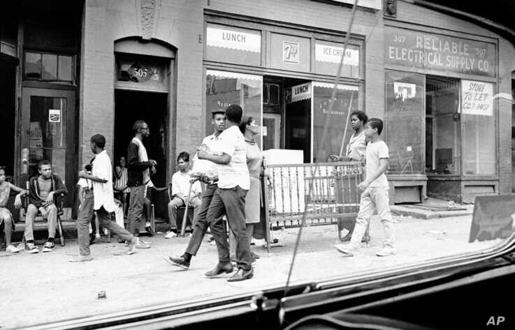 Two men carry furniture looted from a store in Newark, New Jersey, July 14, 1967.