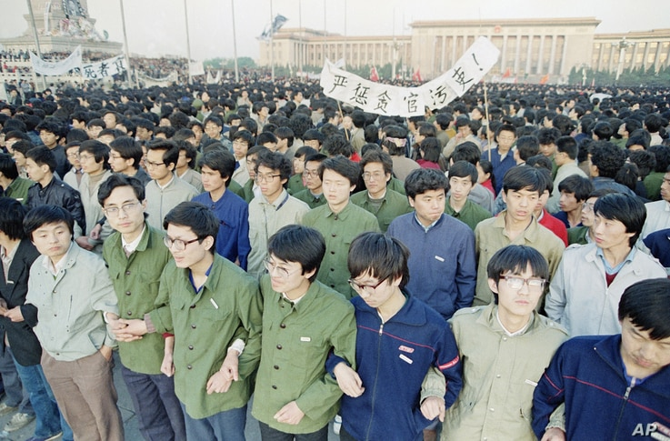 Chinese students link arms in solidarity at dawn on Saturday, April 22, 1989 in Beijing's Tiananmen Square after spending the…