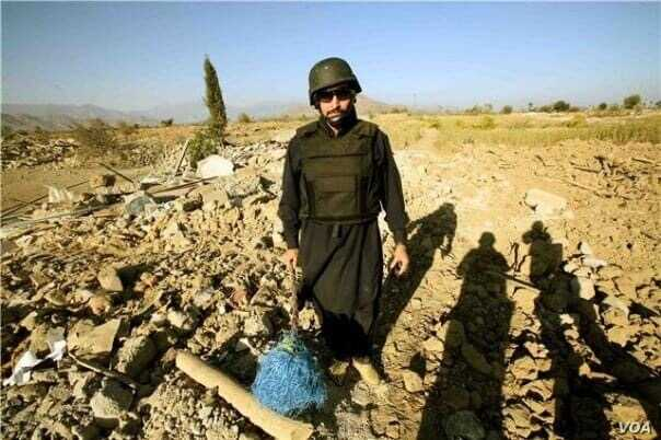 FILE - Pir Shah, from VOA's Deewa Pashto service, in October 2008 in the Bajaur tribal area in Pakistan, standing in debris of a