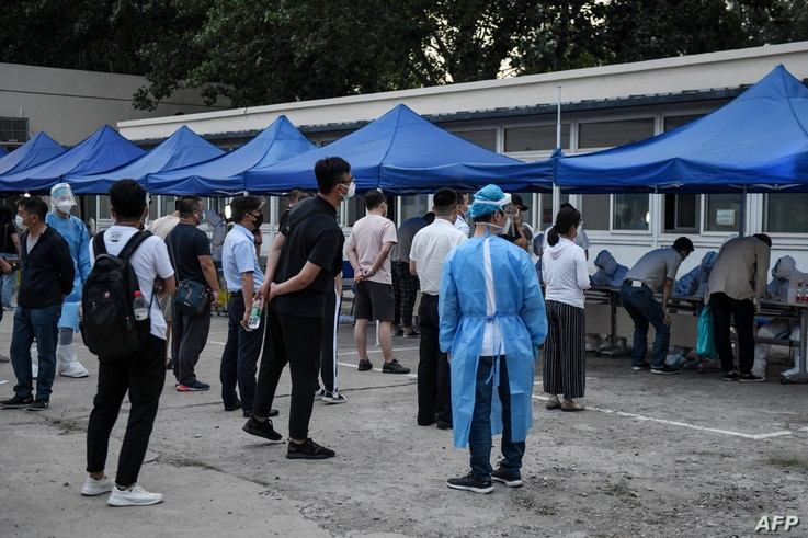 FILE - People who had their cars' license plates recorded near Xinfadi market, a new coronavirus cluster, wait in line for swab tests for the coronavirus, at a testing center in Beijing, China, June 17, 2020.