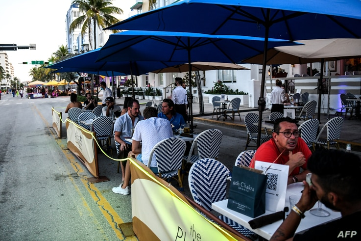 FILE - People eat in an outdoor dining area of a restaurant in Miami Beach, Florida, June 24, 2020.