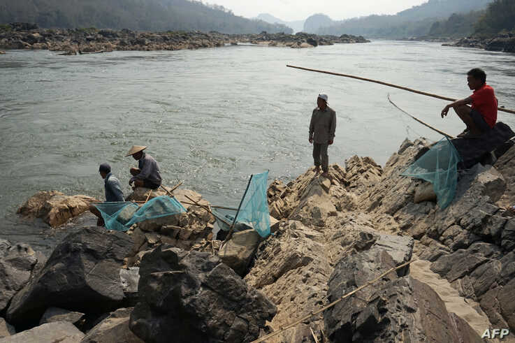 Fishermen lay their nets on the Mekong River near Luang Prabang close to the site of an approved Laos dam site, Feb. 8, 2020.