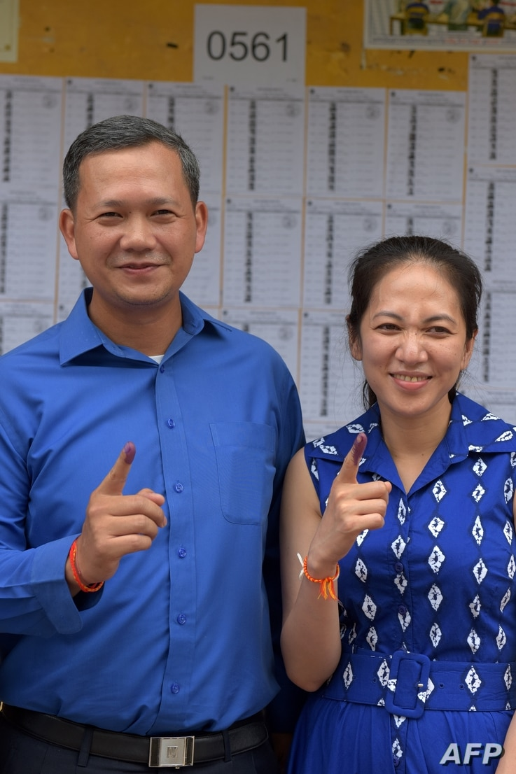 FILE - Son of Cambodian Prime Minister Hun Sen, Hun Manet (L), and his wife Pich Chanmoy show their inked fingers after casting their votes in general elections in Phnom Penh, Cambodia, July 29, 2018.