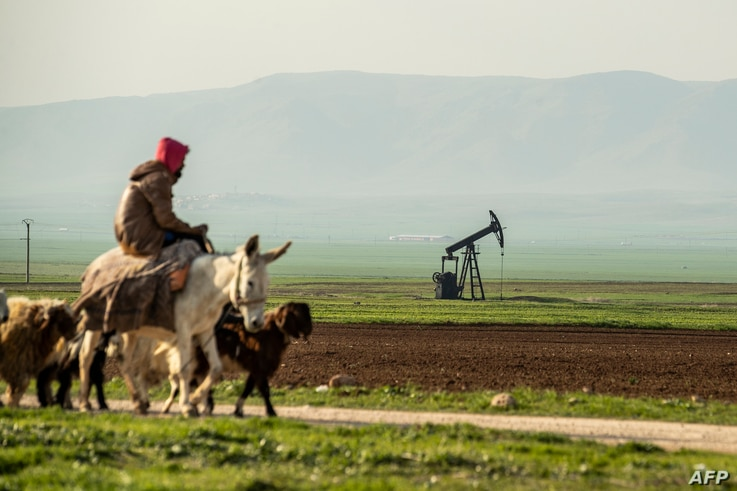 FILE - A shepherd rides a donkey across a pumpjack operating in an oil field in the countryside of al-Qahtaniyah town in Syria's northeastern Hasakeh province, near the Turkish border, March 11, 2020.