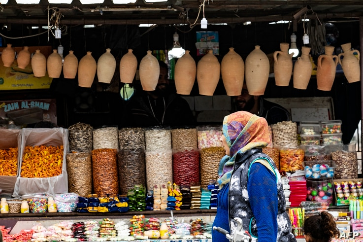 FILE - A woman walks through a market in the Kurdish-majority city of Qamishli, in Syria's northeastern Hasakeh province, Oct. 29, 2019.