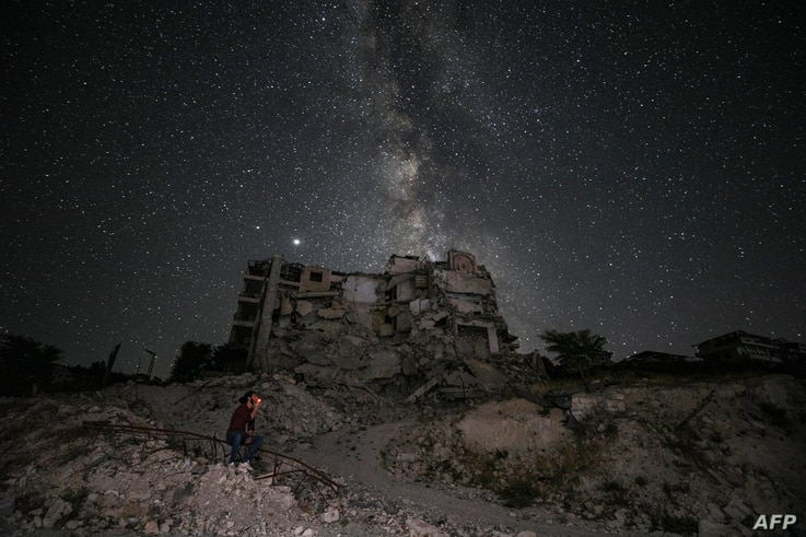 The ruins of Ariha in Syria's rebel-held northwestern Idlib province are lit by the Milky Way, June 27, 2020.