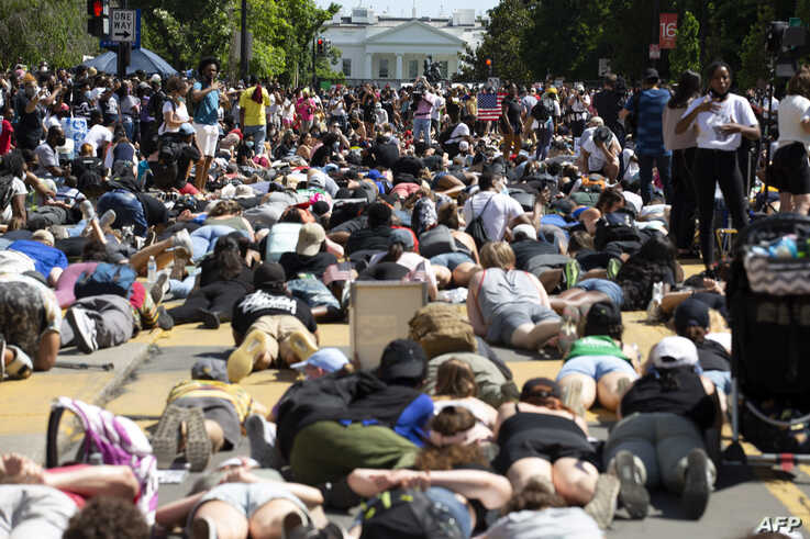 Demonstrators lie on the pavement facing the White House during a rally north of Lafayette Square to protest police brutality and racism, in Washington, June 7, 2020.