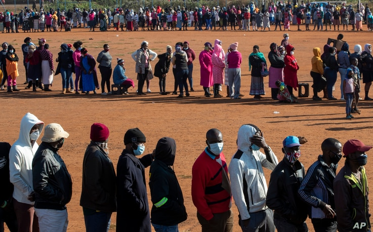 FILE - People affected by the coronavirus economic downturn line up to receive food aid in Pretoria, South Africa, May 20, 2020.