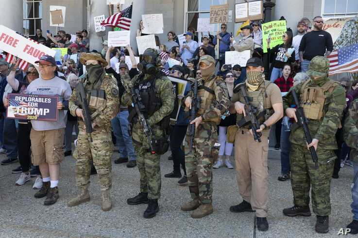 FILE - People, including activists with the Boogaloo movement, rally at the State House in Concord, New Hampshire, May 2, 2020, in a protest unrelated to the George Floyd demonstrations.