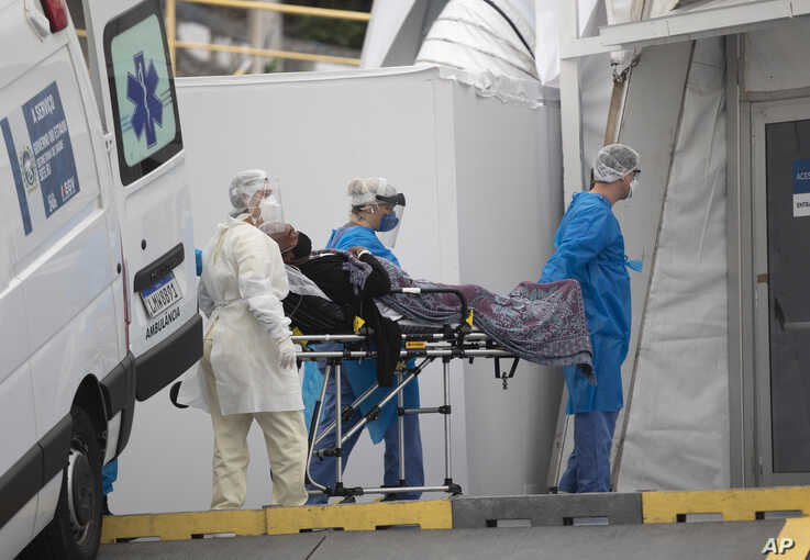 A patient with symptoms related to COVID-19 is brought to a field hospital by workers in full protective gear in Leblon, Rio de Janeiro, Brazil, June 4, 2020.