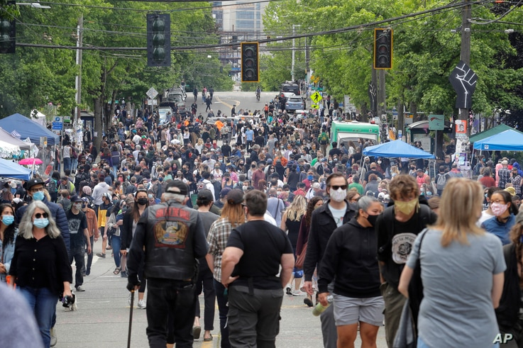 People fill a street June 14, 2020, inside what has been named the Capitol Hill Occupied Protest (CHOP) zone in Seattle, Washington. Protesters calling for police reform and other changes have taken over several blocks near the city's downtown area.
