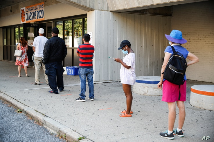 Voters wait in line to cast their ballots in New York's primary election at a polling station inside Yonkers Middle/High School, in Yonkers, New York, June 23, 2020.