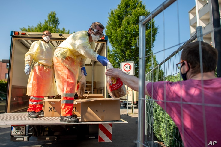 Red Cross staffers wearing face masks and protective clothing distribute bread to residents of a house that has been quarantined, in Verl, Germany, June 21, 2020.