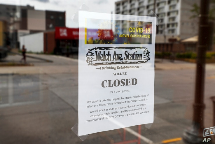 A closed sign is seen in the front window of the Welch Ave Station bar, June 23, 2020, in Ames, Iowa.