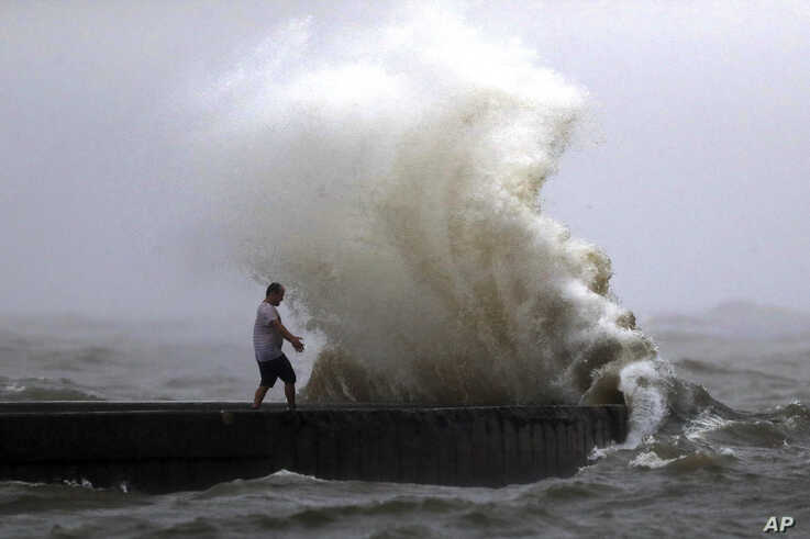 A wave crashes as a man stands on a jetty near Orleans Harbor in Lake Pontchartrain in New Orleans, June 7, 2020, as Tropical Storm Cristobal approaches the Louisiana Coast.