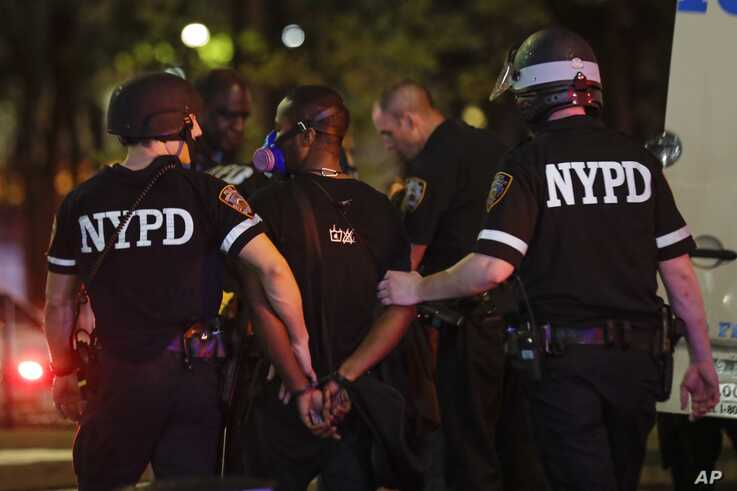 New York Police Department officers escort a protester after he was arrested at a rally calling for justice over the death of George Floyd, in the Brooklyn borough of New York, June 3, 2020.