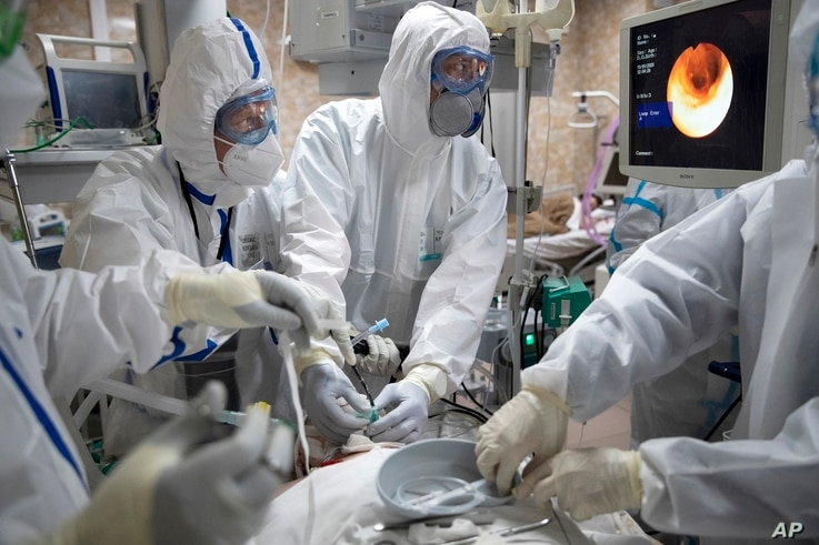 FILE - Doctors perform tracheal intubation on a coronavirus patient for artificial lung respiration at an intensive care unit of the Filatov City Clinical Hospital in Moscow, Russia, May 15, 2020.