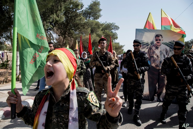 FILE - Fighters of the Syrian Democratic Forces (SDF) march during a rally in al-Qahtaniyah, Syria, Oct. 7, 2019.
