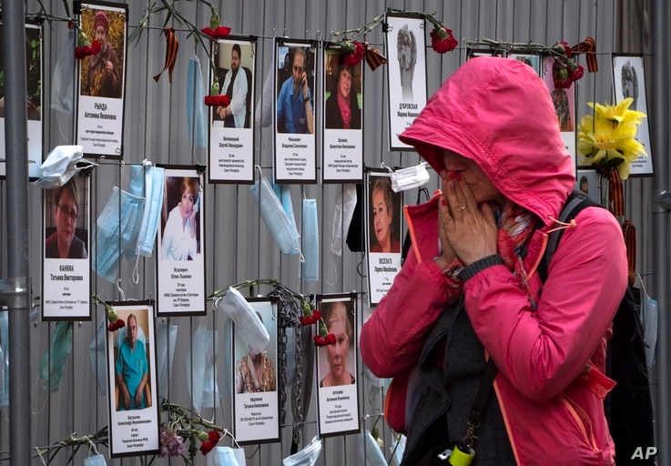 FILE - A woman reacts as she walks past photos of St. Petersburg's medical workers who died from the coronavirus after being infected at work, at a makeshift memorial at a local health department in St. Petersburg, Russia, May 20, 2020.