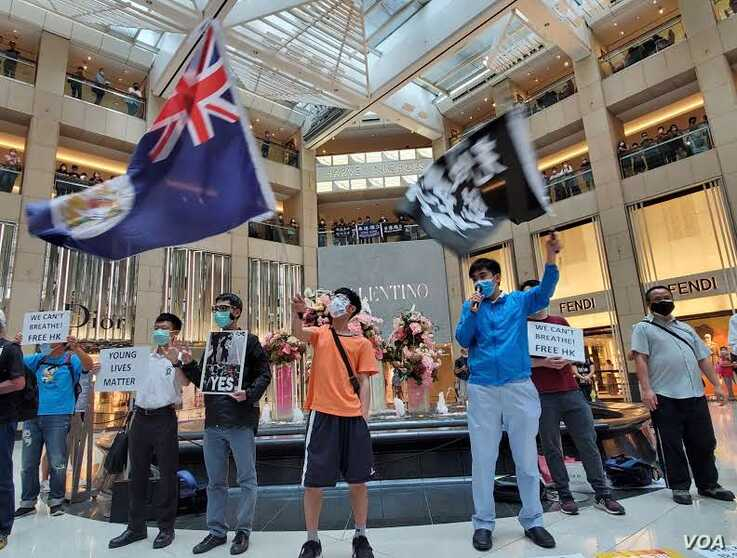 Activists chant slogans, display a British colonial flag and banners at a protest in Landmark shopping mall