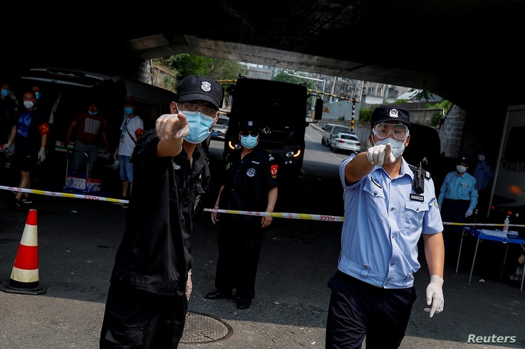 FILE - Police and security personnel direct a photographer to refrain from taking pictures at a a cordon isolating a residential area near Xinfadi Market, a new coronavirus hotspot in Beijing, China, June 20, 2020.