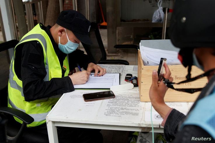 FILE - A man holds up his smartphone to share health app data as a government worker notes down his phone number at a checkpoint in Beijing, China, April 29, 2020.