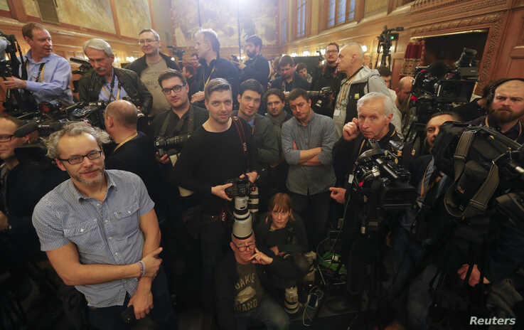 FILE - Journalists wait for the start of a news conference by Hungarian Prime Minister Viktor Orban and Russian President Vladimir Putin, in Budapest, Hungary, Feb. 2, 2017.