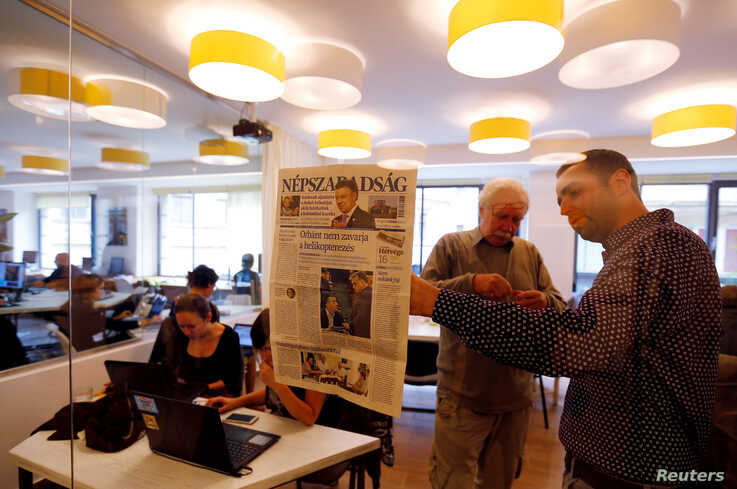 FILE - Journalists of the newspaper Nepszabadsag, which was shut down amid cries of a crackdown by Prime Minister Viktor Orban's government, paste a copy of its last issue onto a glass wall in a makeshift newsroom in Budapest, Hungary, Oct. 10, 2016.
