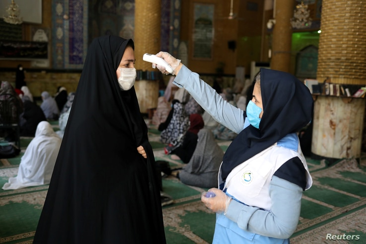 FILE - A woman wearing a protective face mask checks the temperature of a worshipper, also with mask, ahead of Friday prayers at Qarchak Jamee Mosque, in Qarchak, Iran, June 12, 2020.