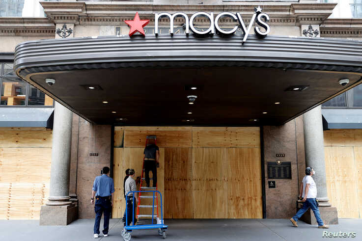 Workers board up the Macy's store in Herald Square after it was damaged and looted by protesters who rallied against the death in Minneapolis police custody of George Floyd, in the Manhattan borough of New York City, June 2, 2020.