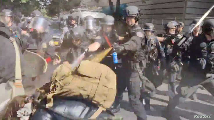 Police use pepper spray against protesters in Portland, Oregon, May 31, 2020, in this still image taken from video obtained by Reuters.
