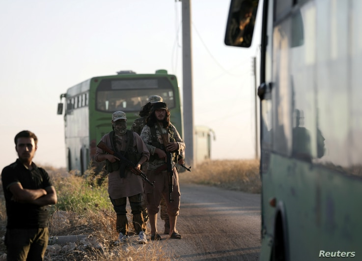 FILE - Rebels from the Hayat Tahrir al-Sham group are seen near buses, outside the villages of al-Foua and Kefraya, Idlib province, Syria, July 18, 2018.
