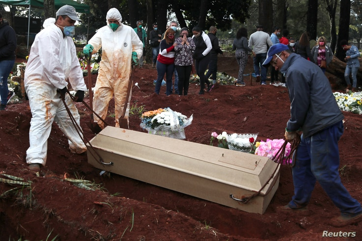 Relatives react as gravediggers bury the coffin of Eriveltu Aparecido Spada, 57, suspected to have died from the coronavirus disease (COVID-19) at Vila Formosa cemetery, in Sao Paulo, Brazil, June 27, 2020.
