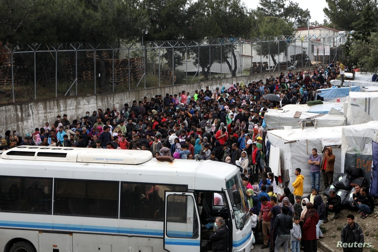 Migrants from the Moria camp wait to board busses to the port from where they will be transferred to the mainland as a precaution against the spread of the coronavirus disease (COVID-19) outbreak, on the island of Lesbos, Greece, May 3, 2020.