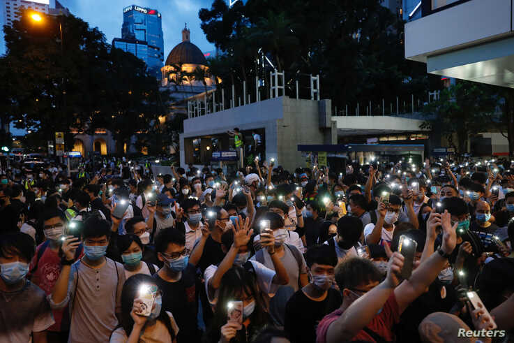 Pro-democracy demonstrators march holding their phones with flashlights on during a protest to mark the first anniversary of a mass rally against the now-withdrawn extradition bill, in Hong Kong, China, June 9, 2020.